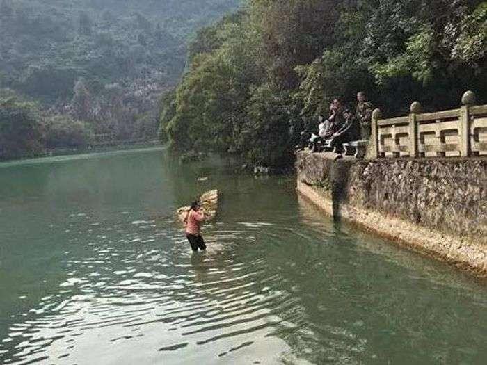 Китаянка пірнула в крижану воду, щоб дістати впав iPhone (4 фото)